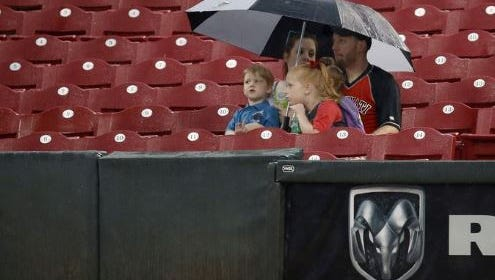 Fans wait under cover from the rain during a delay prior to a May 12, 2015, Reds game against the Atlanta Braves.