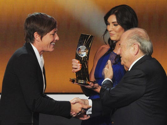 """FILE - In this Jan. 7, 2013, file photo, Abby Wambach, left, of the United States is presented the FIFA Women's World Player of the Year award by Hope Solo, center, goalkeeper of the U.S. team, and FIFA President Sepp Blatter, right, during the FIFA Ballon d'Or Gala held at the Kongresshaus in Zurich, Switzerland. Solo told a Portuguese newspaper that former FIFA President Blatter sexually assaulted her at the ceremony. In an interview published Friday, Nov. 10, 2017, in the newspaper Expresso, Solo said Blatter """"grabbed"""" her inappropriately on her rear end shortly before the two appeared onstage at the awards event. (AP Photo/Keystone, Steffen Schmidt, File)"""