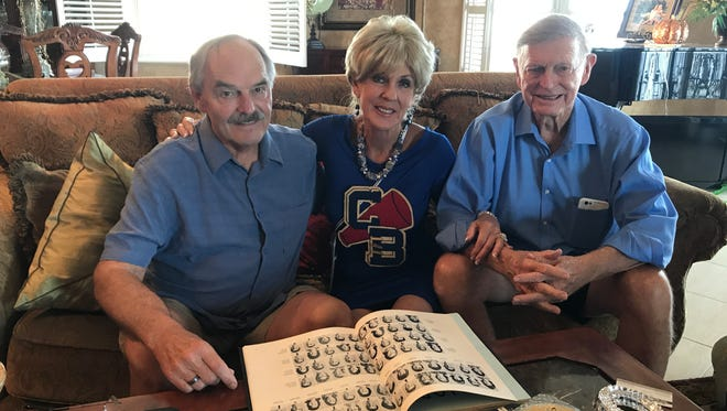 Charley Priddy, Susie Wasdin and Tom Wasdin look through an old Cocoa Beach High School yearbook as they prepare for the coming class reunion.