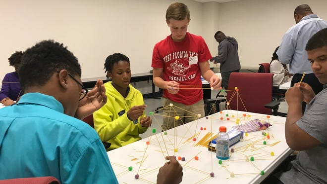 Students work together to build a tower constructed with ordinary household items of uncooked spaghetti noodles and gum drop candy – to see which group's tower could stand upright for 30 seconds or longer.