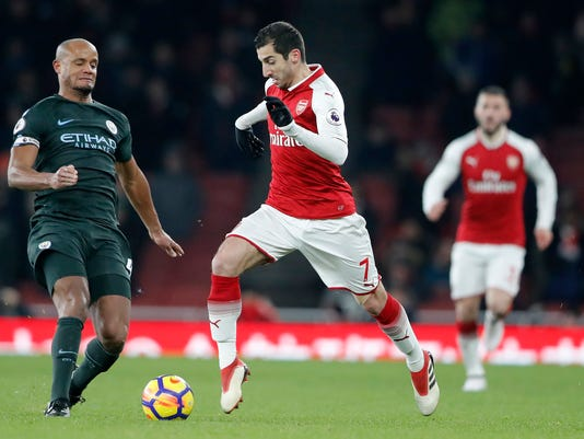 Arsenal's Henrikh Mkhitryan, center, is challenged by Manchester City's Vincent Kompany during the English Premier League soccer match between Arsenal and Manchester City at the Emirates stadium in London, Thursday, March 1, 2018.(AP Photo/Frank Augstein)