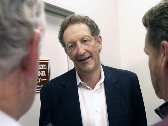 Larry Baer's wife, Pam, was seated in a chair when