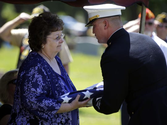 "Sgt. Elden W. Grimm, a U.S. Marine from Menasha who died in battle during World War II is buried with full military honors Saturday at Oak Hill Cemetery in Neenah. His niece, Margaret Kersten is presented with the flag by Capt. Nicholas Pecoraro. In October 2016, the Defense POW/MIA Accounting Agency, with the aid of new forensic technology, resumed the uncovering of ""unknowns"" from the battle of Tarawa and Grimm was identified less than a year later."