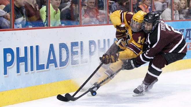 Minnesota's Tom Serratore, left, and Union's Jeff Taylor, right, battle for the puck along the boards during the second period of an NCAA men's college hockey Frozen Four tournament game on Saturday.
