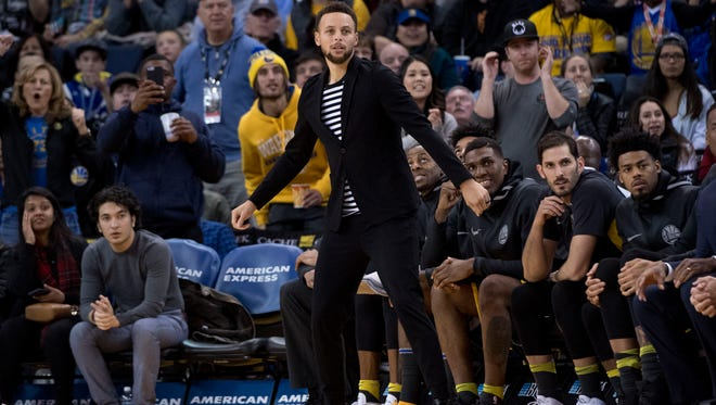 Golden State Warriors guard Stephen Curry (30) watches from the bench during the third quarter against the Denver Nuggets at Oracle Arena.