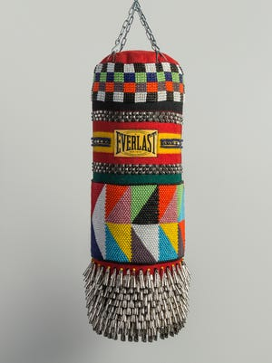 """""""American Girl"""" by Jeffrey Gibson, 2013. Found punching bag, wool blanket, glass beads, steel studs, artificial sinew, tin jingles and chain. Part of the exhibit """"Beautiful Games: American Indian Sport and Art"""" at the Heard Museum."""