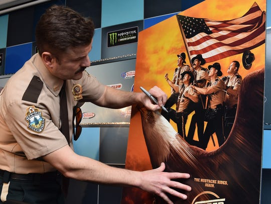 Actor Steve Lemme signs a Super Troopers 2 poster after a press conference prior to the Monster Energy NASCAR Cup Series Auto Club 400 at Auto Club Speedway on March 18, 2018 in Fontana, California. (Photo by Jonathan Moore/Getty Images)