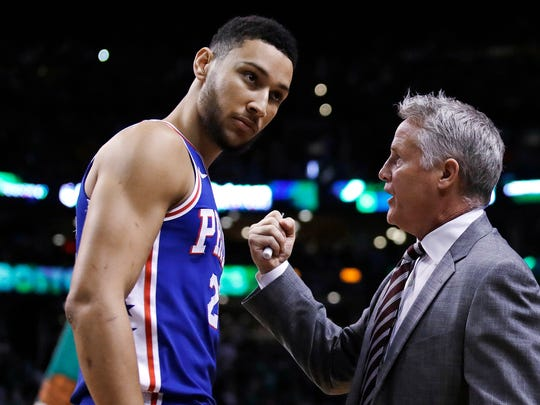 Sixers guard Ben Simmons consults with head coach Brett Brown during a 2018 playoff game.