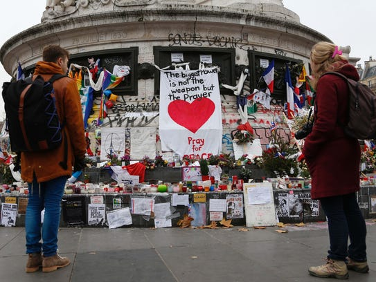 People gather in front of a makeshift memorial in Place