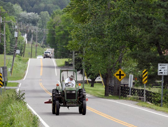 A tractor shares the road with cars on Old Hillsboro