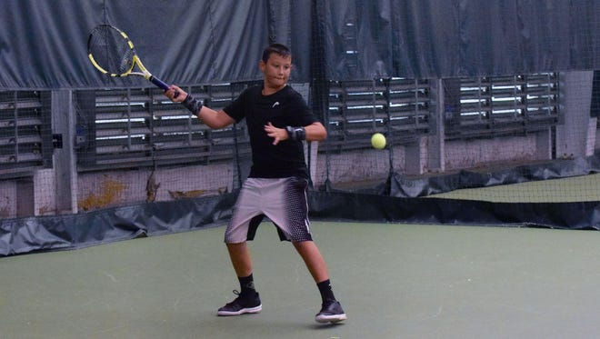 Chase Pullin, 12, hits a return to Mark Gordon during their junior boys singles final at the Augusta Health/News Leader Tennis Tournament, held Thursday at the Augusta Health Fitness Center. Pullin won the match in straight sets.