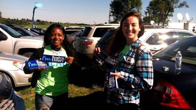 Ready for Hillary volunteers Clarke Conner and Aya Kantorovich, both of Washington, D.C., hand out bumper stickers Sunday to people arriving at the Harkin Steak Fray in Indianola, Iowa