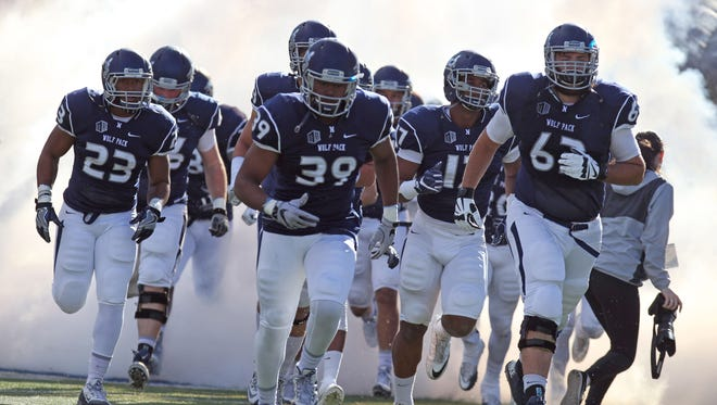 The Wolf Pack football team runs out to the field for its game against Utah State this season.