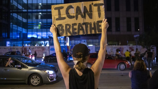 "A protester holds a sign that reads ""I can't breath"" during a demonstration t for racial equality and justice in the wake of George Floyd's death earlier this year."