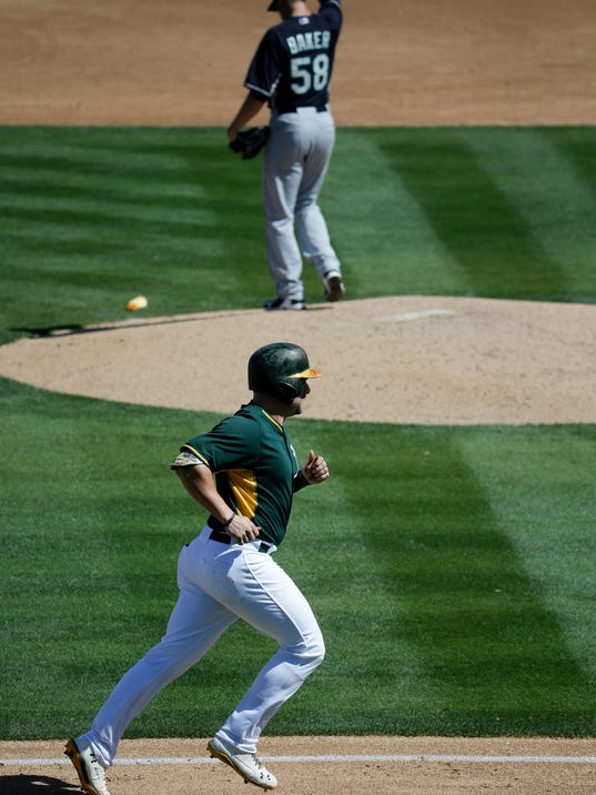 Oakland Athletics' Stephen Vogt, bottom, rounds the bases after a two-run home run as Seattle Mariners starting pitcher Scott Baker, top, looks away during the third inning of a spring exhibition baseball game in Phoenix, Saturday, March 22, 2014. (AP Photo/Chris Carlson)