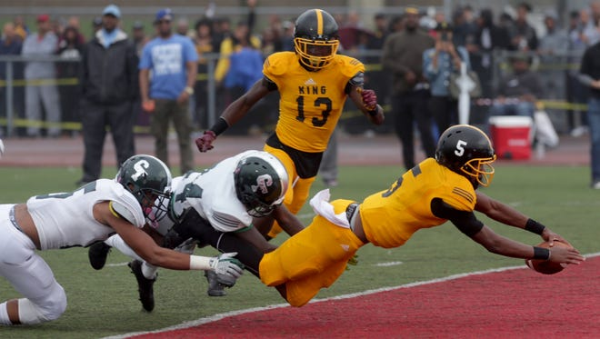 Detroit King quarterback Dequan Finn dives into the end zone against Detroit Cass Tech to make the score 14-0 in the first quarter during the Detroit Public School League semifinal at Detroit Northwestern on Saturday, Oct.14, 2017. King won, 17-7.