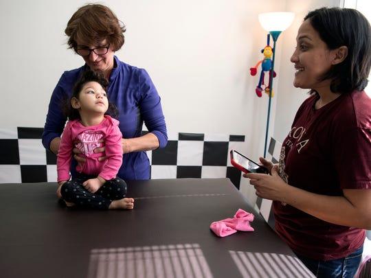 Claudia Funes mira a su hija, Darah, 1, que nació con microcefalia causada por el virus del Zika, durante una sesion con Ewa Lobo, una fisioterapeuta, viernes, el 16 de  marzo 2018.