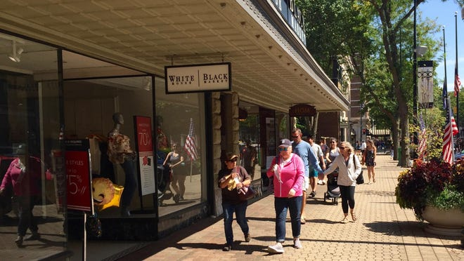 Labor Day shoppers walk along Eighth Street in front of White House Black Market in Holland.