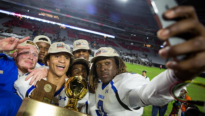 Chandler senior quarterback Bryce Perkins (right) takes a selfie with his teammates at the University of Phoenix Stadium after their win at the division 1 high school football state championships November 28, 2014 in Glendale.