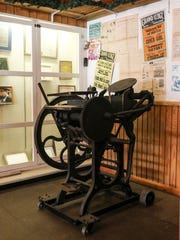 An old printing press inside the Welch Historical Museum