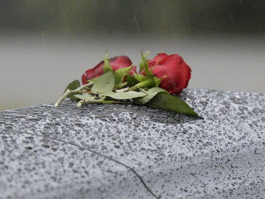 A pair of roses sit atop a casket at Florida Memorial