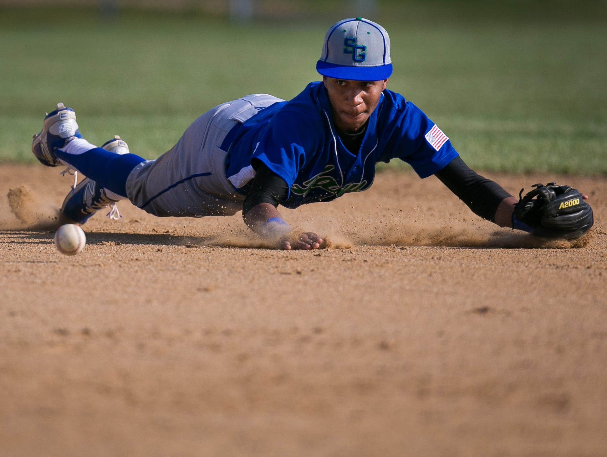 St. Georges second baseman Robert Shorts dives for the ground ball.