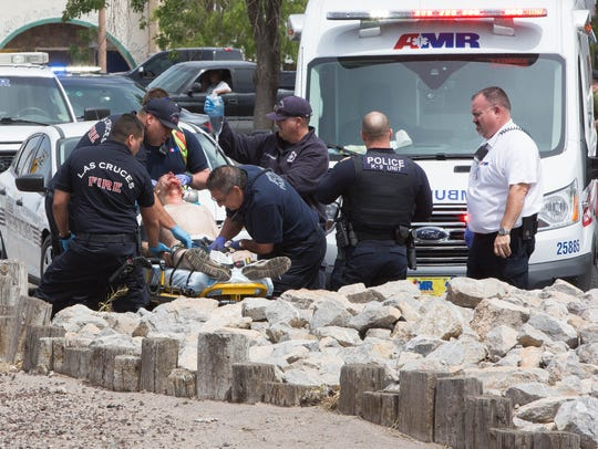 Las Cruces firemen and American Medical Response ambulance personnel load a gunshot victim into an ambulance in April 2017.