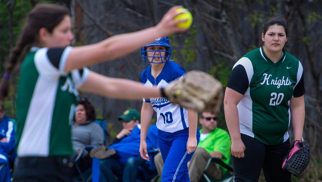 Missisquoi's Tricia Wright, center, watches Rice pitcher Rachel Chicoine, left, wind up in South Burlington on Thursday, May 19, 2016.