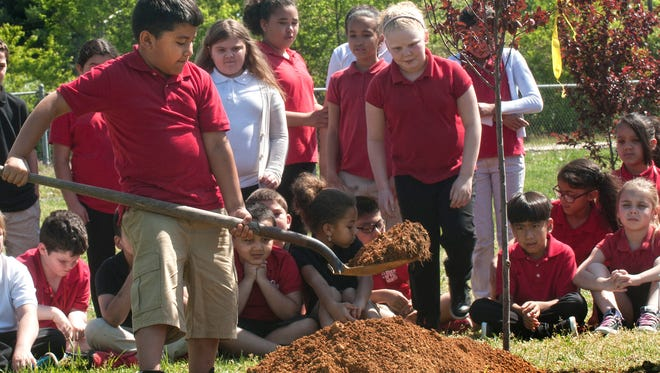 Fourth Grade student, Reynolds Almeida plants a tree in school grounds during Arbor Day celebrations at Durand Elementary School in Vineland.