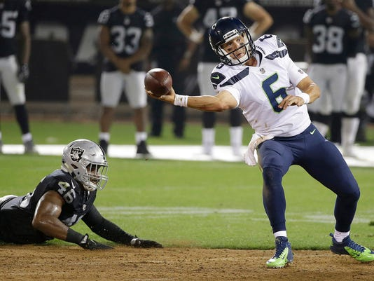 Seattle Seahawks quarterback Austin Davis (6) passes in front of Oakland Raiders linebacker LaTroy Lewis (46) during the second half of an NFL preseason football game in Oakland, Calif., Thursday, Aug. 31, 2017. (AP Photo/Eric Risberg)