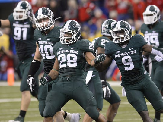 MSU's defense celebrates after Denicos Allen makes a fourth down stop of Ohio State quarterback Braxton Miller late in MSU's 34-24 win at the Big Ten Championship football game in 2013. That season was the beginning of a 36-5 three-year run for the Spartans.