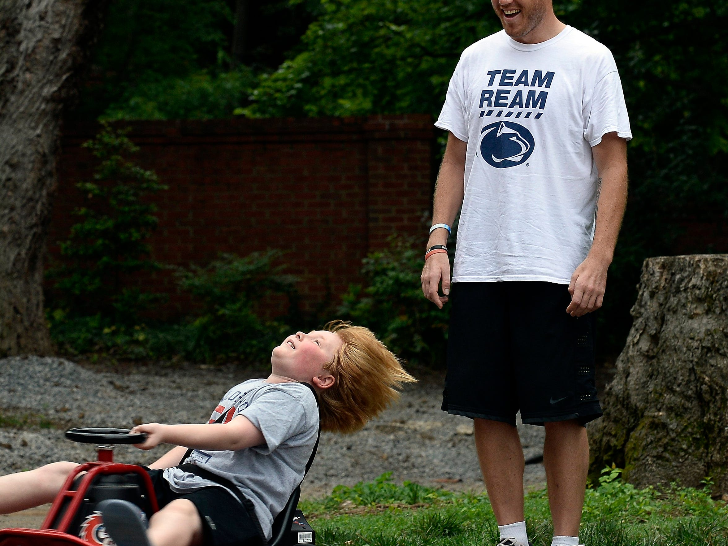 Britton Busbee, 9, shows Tim Shaw how to spin on a