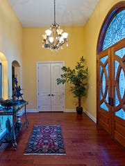 An amazing leaded glass double door leads into a spacious
