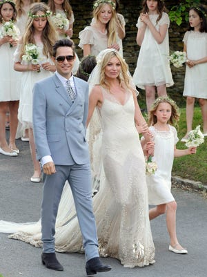 In this July 2011 file photo, British model Kate Moss and British guitarist Jamie Hince pose for photographers with unidentified bridesmaids, after their wedding in the village of Southrop, England. Brides may want to take a page from the playbook of the supermodel Moss, who asked her friend John Galliano to make her a vintage style wedding dress, and the designer used Zelda Fitzgerald as inspiration. The cream-colored, bias cut gown featured an Art Deco motif along the bottom, and was embroidered with gold, spangled with gold paillettes.