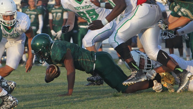 Island Coast ball carrier Jerry Cambric moves forward for positive yardage against Fort Myers Friday in Cape Coral.
