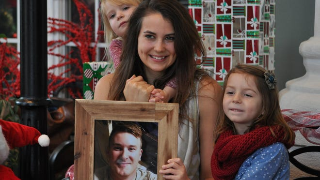 Rachel Friedrich poses with daughters Madelyn, 5, and Harper, 3, and picture of her deployed husband during Fort Polk's 2015 Very Merry Military Mini Sessions, held Saturday.