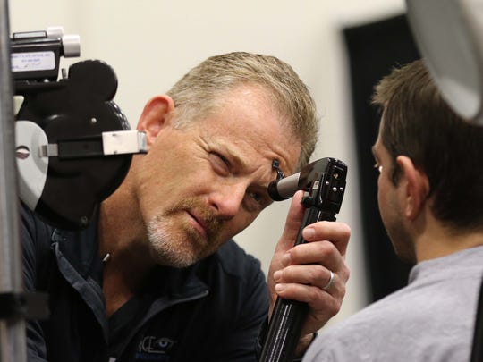 Dr. David M. Pierce performs an extensive eye exam on a young man at the Hope Connection event at the Expo Center in Springfield on Nov. 16, 2016.