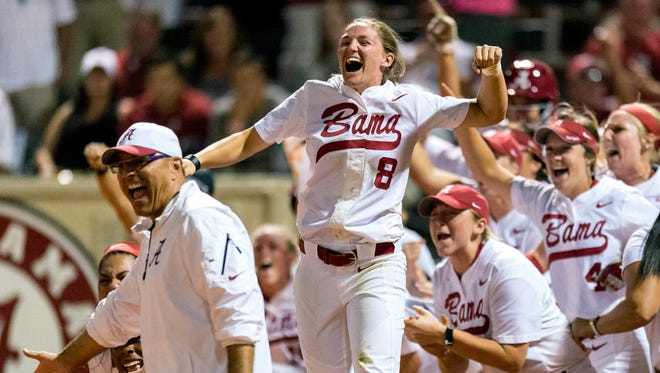 Alabama outfielder Haylie McCleney (8) leaps in the air in celebration of infielder Marisa Runyon's grand slam home run during an NCAA college softball Super Regional game against Oklahoma on Saturday in Tuscaloosa.