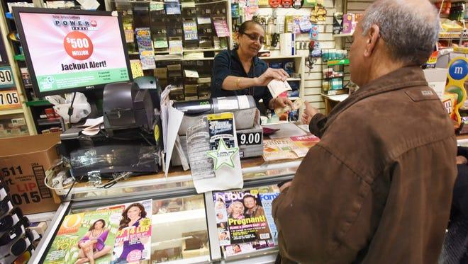 Vilas Patel sells a Powerball ticket to Pravin Bhatt, right, at Leprechaun News in Rutherford, N.J., last week.