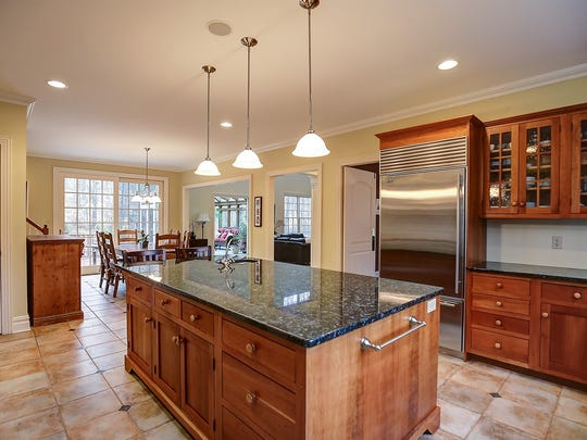 The kitchen has stone tile floors, a large center island with seating and cherry cabinets with granite counters, stainless-steel appliances, pedant and recessed lighting and an eating area with sliding French doors to the multitier deck.