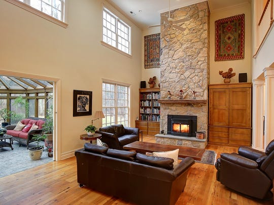 The two-story family room has a floor-to-ceiling filedstone