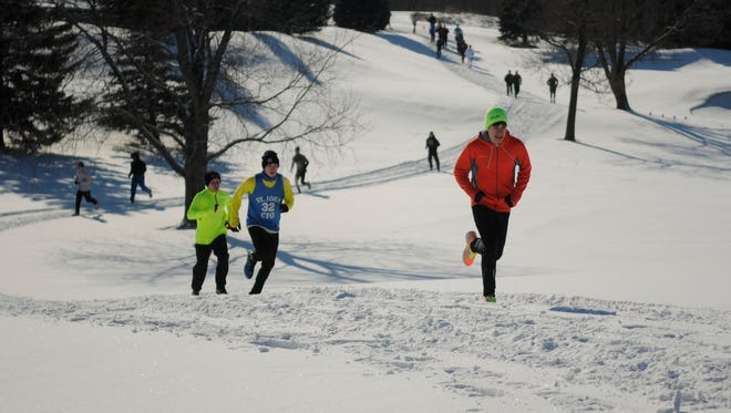 From right, Zack Hietpas, Eric Schiller, and Matt Lancour, all from Little Chute, run up a slope during the First Annual Winter Warrior 5K at Mid Vallee Golf Course in 2012.