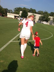 Ole Miss soccer player Sara Coleman walks her daughter, Parker, off the field.