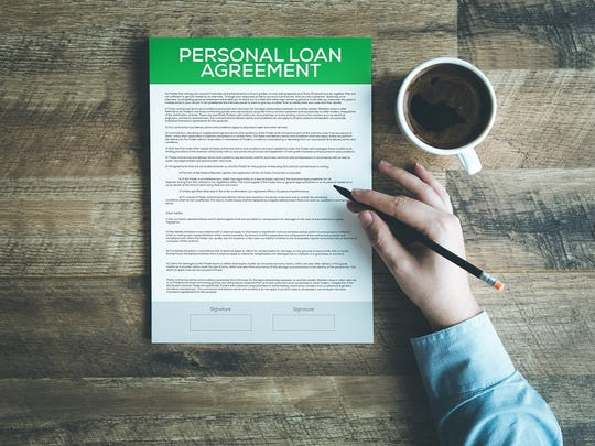 Hand holding a pencil and hovering over a personal loan agreement.