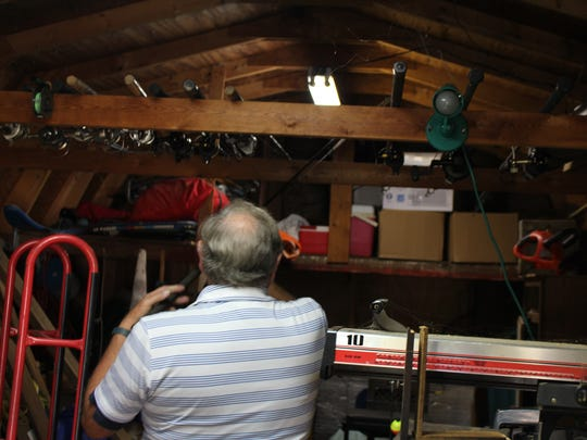 Howard Martin, who recently caught a fish in every state, puts one of his fishing rods away in a shed.