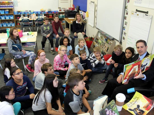 "Webster School District Supetintendent Carmen Gumina reads ""The Bear Ate Your Sandwich"" to Erin Lantzer's (rear, at right) Schlegel Road Elementary School fifth-grade class."