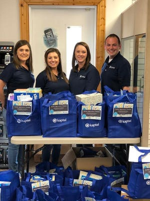 Kaptel's Abbeville store customer service team pose with the donated teachers' supplies.