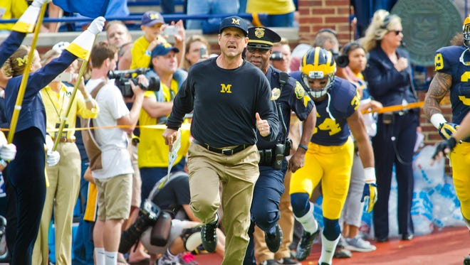 Michigan football coach Jim Harbaugh leads his players out of the tunnel in Ann Arbor on Saturday, Sept. 26, 2015.