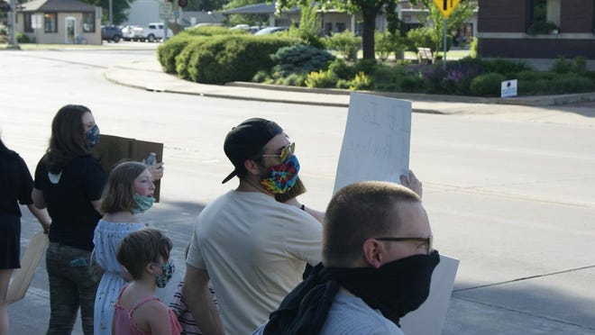 A group of people wearing masks hold up protest signs during a protest at the gates of Chandler Park Friday. The protest was established by a local resident and her son in protest the day that unarmed Minnesota resident George Floyd died after officer Derik Chauvin knelt on his neck for 8 minutes and 46 seconds.