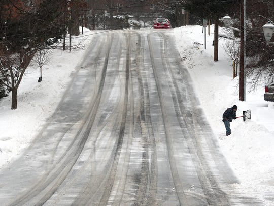 A man shovels snow from his driveway on an empty Colles Avenue in Morristown as the impending snowstorm heading for New Jersey was a bust for Morris County. January 27, 2015. Morristown, N.J.